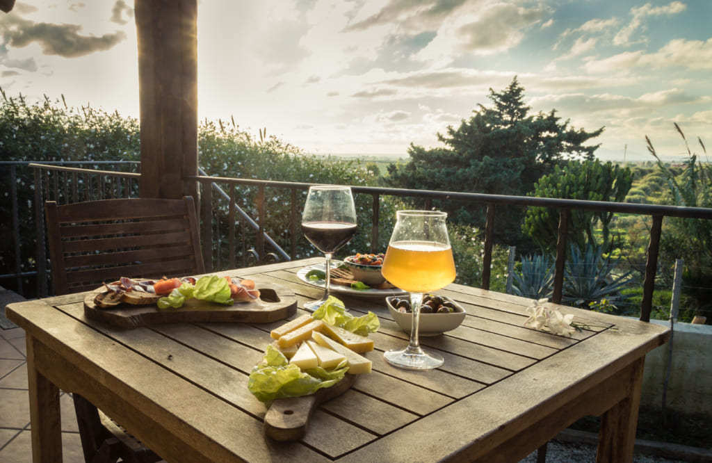 Appetizer for two on a terrace at sunset. Landscape view. Beer glass, wine glass, cheese, olives, bread, lettuce and ham on a wooden table