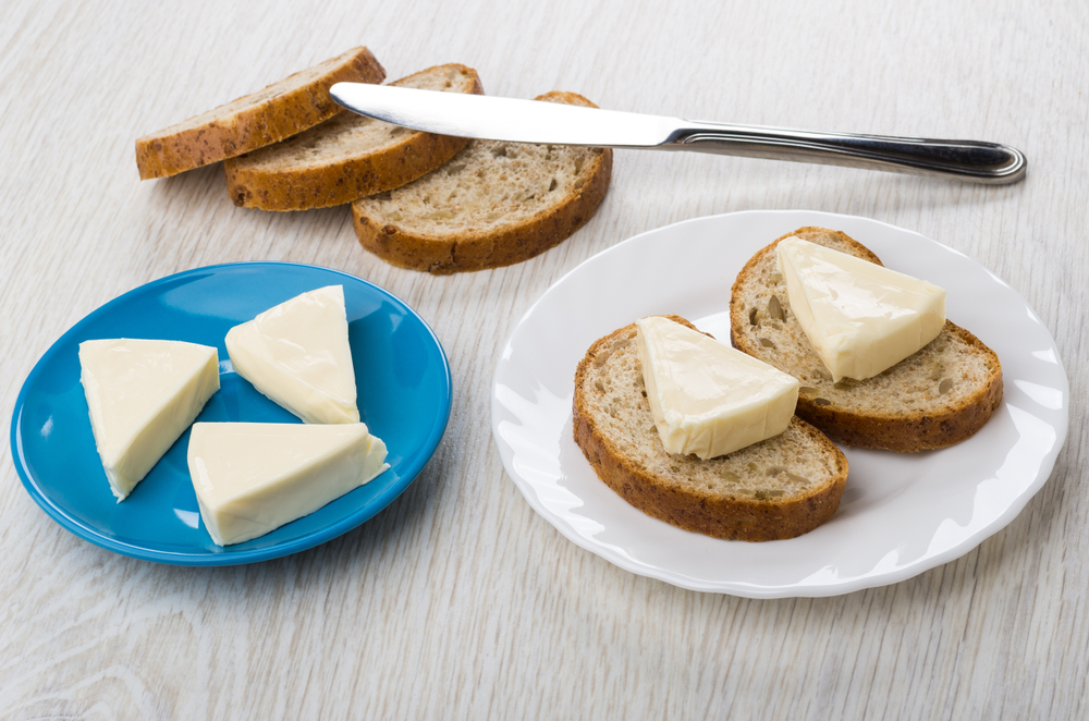 Two sandwiches with melted cheese in white plate , cheese in saucer, table knife and bread on light wooden table